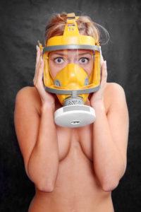 Terrified girl in yellow gas mask. Environmental metaphor.