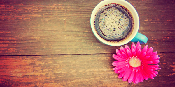 a cup of coffee and a flower on a wooden texture background tone
